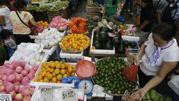 A Filipino woman receives her change as she buys round fruits at a makeshift stand in downtown Manila, Philippines on Saturday Dec. 31, 2011. Many Filipinos believe that having 12 round fruits of different kinds &#40;or pieces&#41; on the family table will bring good luck during the New Year. &#40;AP Photo&#47;Aaron Favila&#41; <span class=meta>(AP Photo&#47; Aaron Favila)</span>
