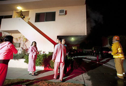 Residents stand outside of their apartment after a car fire in a carport forced their evacuation in the Sherman Oaks neighborhood of Los Angeles on Monday, Jan. 2, 2012. For the fifth night in a row, a spate of arson fires has sent firefighters scrambling to extinguish car fires in the Hollywood, Hollywood Hills, Studio City, and Sherman Oaks neighborhoods of Los Angeles. The Los Angeles Fire Department confirms a person of interest has been detained and is being questioned in connection with the arson spree. &#40;AP Photo&#47;Dan Steinberg&#41; <span class=meta>(AP Photo&#47; DAN STEINBERG)</span>