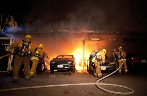 Los Angeles Fire Department firefighters extinguishes numerous cars on fire in a carport in the Sherman Oaks neighborhood of Los Angeles on Monday, Jan. 2, 2012. For the fifth night in a row, a spate of arson fires has sent firefighters scrambling to extinguish car fires in the Hollywood, Hollywood Hills, Studio City, and Sherman Oaks neighborhoods of Los Angeles. The Los Angeles Fire Department confirms a person of interest has been detained and is being questioned in connection with the arson spree. &#40;AP Photo&#47;Dan Steinberg&#41; <span class=meta>(AP Photo&#47; DAN STEINBERG)</span>