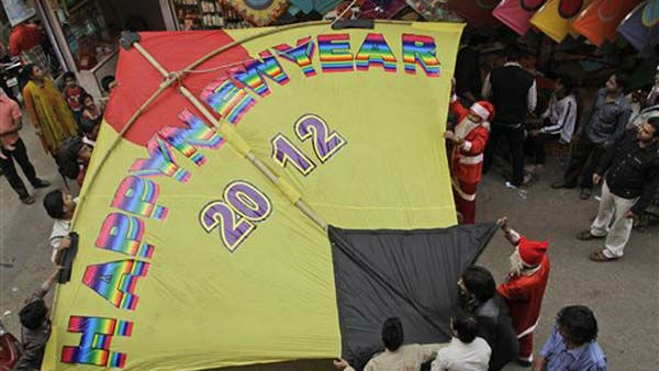 Indian men carry a giant kite to hang on the facade of a building housing a kite shop to welcome the New Year in Ahmadabad, India, Saturday, Dec. 31, 2011. &#40;AP Photo&#47;Ajit Solanki&#41; <span class=meta>(AP Photo&#47; Ajit Solanki)</span>