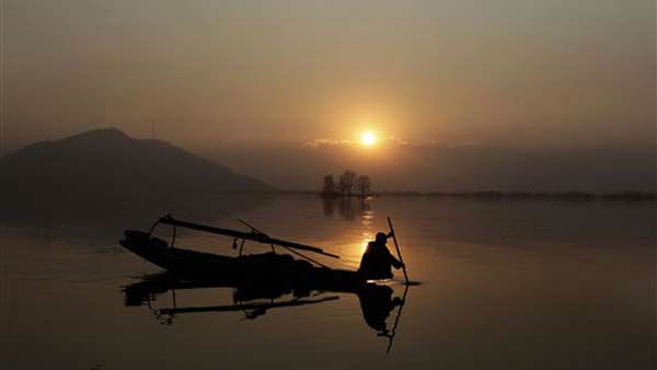 A Kashmiri fisherman rows his boat on the Dal Lake as the sun sets in Srinagar, India, Saturday, Dec. 31, 2011. Most parts of northern India experienced cold but clear weather on new year&#39;s eve. &#40;AP Photo&#47; Dar Yasin&#41; <span class=meta>(AP Photo&#47; Dar Yasin)</span>