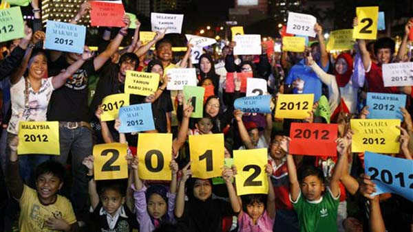 Malaysian people hold placards reading &#34;2012&#34; during New Year&#39;s Eve celebrations at Independence Square in Kuala Lumpur, Malaysia, Saturday, Dec. 31, 2011. &#40;AP Photo&#47;Lai Seng Sin&#41; <span class=meta>(AP Photo&#47; Lai Seng Sin)</span>
