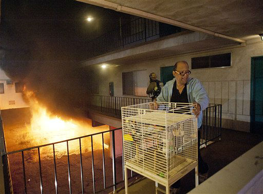 Los Angeles Fire Department firefighters assist a man out of his apartment along with a cage of birds as multiple cars burn in a carport in the Sun Valley neighborhood of Los Angeles on Saturday, Dec. 31, 2011. For the third night in a row, a rash of arson fires has sent firefighters scrambling to extinguish car fires in various neighborhoods in Los Angeles. Most of the fires on this night occurred in the San Fernando Valley. &#40;AP Photo&#47;Dan Steinberg&#41; <span class=meta>(AP Photo&#47; Dan Steinberg)</span>