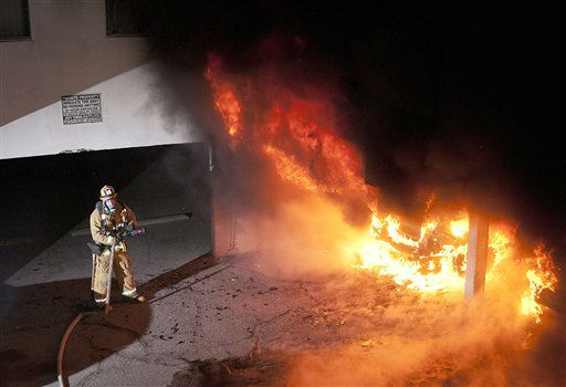 A Los Angeles Fire Department firefighter waits for water to extinguish multiple cars on fire in a carport in the Sun Valley neighborhood of Los Angeles on Saturday, Dec. 31, 2011. For the third night in a row, a rash of arson fires has sent firefighters scrambling to extinguish car fires in various neighborhoods in Los Angeles. &#40;AP Photo&#47;Dan Steinberg&#41; <span class=meta>(AP Photo&#47; Dan Steinberg)</span>
