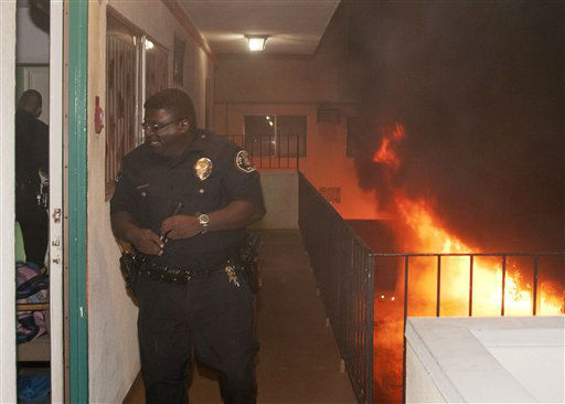 Los Angeles Police Department officers evacuate residents of an apartment building as multiple cars burn in a carport in the Sun Valley neighborhood of Los Angeles on Saturday, Dec. 31, 2011. For the third night in a row, a rash of arson fires has sent firefighters scrambling to extinguish car fires in various neighborhoods in Los Angeles. &#40;AP Photo&#47;Dan Steinberg&#41; <span class=meta>(AP Photo&#47; Dan Steinberg)</span>
