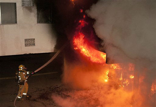 "<div class=""meta ""><span class=""caption-text "">A Los Angeles Fire Department firefighter extinguishes multiple cars on fire in a carport in the Sun Valley neighborhood of Los Angeles on Saturday, Dec. 31, 2011. For the third night in a row, a rash of arson fires has sent firefighters scrambling to extinguish car fires in various neighborhoods in Los Angeles. Most of the fires on this night occurred in the San Fernando Valley. (AP Photo/Dan Steinberg) (AP Photo/ Dan Steinberg)</span></div>"
