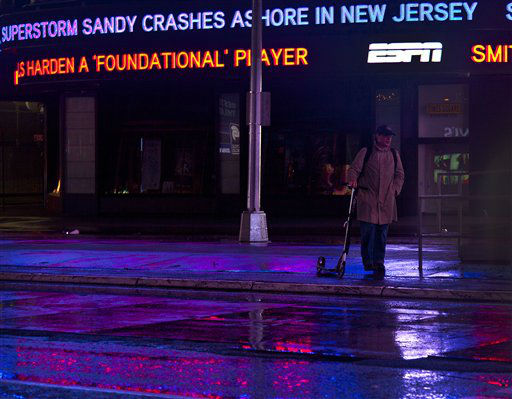 A lone pedestrian stand with his scooter near a message about superstorm Sandy in New York&#39;s Times Square, early Tuesday, Oct. 30, 2012. For New York City, Sandy was not the dayslong onslaught many had feared, and the wind and rain that sent water sloshing into Manhattan from three sides began dying down within hours. Still, the power was out for hundreds of thousands of New Yorkers and an estimated 6.2 million people altogether across the East.   <span class=meta>(AP Photo&#47; CX Matiash)</span>