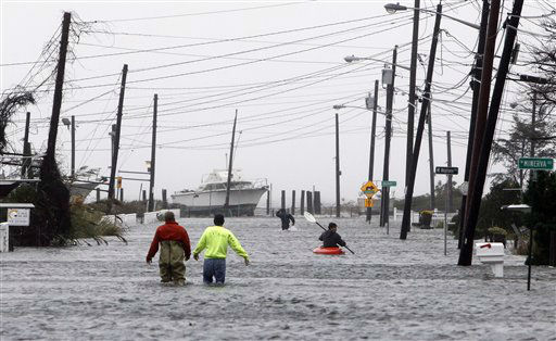 People wade and paddle down a flooded street as Hurricane Sandy approaches, Monday, Oct. 29, 2012, in Lindenhurst, N.Y. Gaining speed and power through the day, the storm knocked out electricity to more than 1 million people and figured to upend life for tens of millions more.   <span class=meta>(AP Photo&#47; Jason DeCrow)</span>