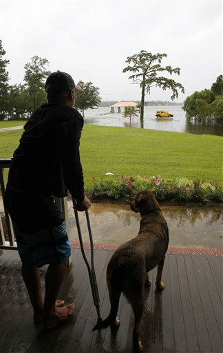 Tommy Hartley and his dog Hercules watch people drive through a flooded area from his front porch along the Dog River in Mobile, Ala. on Wednesday, Aug. 29, 2012.  Hurricane Isaac has dumped more than five inches of rain on the Alabama coast and knocked out power to some residents, but it hasn&#39;t interrupted the everyday life of others.  Residents of Dauphin Island lost power, but they also escaped the worst of Isaac. The weather service reports wind gusts of 47 mph.  <span class=meta>(AP Photo&#47; Butch Dill)</span>