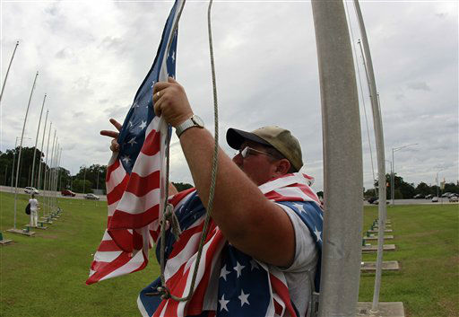 Hubert Darby works to lower American Flags in Robertsdale, Ala, as residents prepare for Tropical Storm Isaac, Monday, Aug. 27, 2012. With its massive size and ponderous movement, a strengthening Isaac could become a punishing rain machine depending on its power, speed and where it comes ashore along the Gulf Coast.  <span class=meta>(AP Photo&#47; John Bazemore)</span>