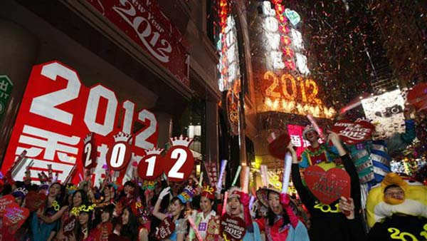 Revellers wave during the New Year celebrations in Hong Kong&#39;s Times Square Sunday, Jan. 1, 2012. &#40;AP Photo&#47;Kin Cheung&#41; <span class=meta>(AP Photo&#47; Kin Cheung)</span>