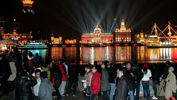 Visitors walk near the river front promenade called &#39;the Bund, one of the most popular tourist destinations in town, is illuminated to celebrate the New Year on Saturday, Jan. 1, 2012 in Shanghai, China.  &#40;AP Photo&#41; <span class=meta>(AP Photo&#47; STR)</span>