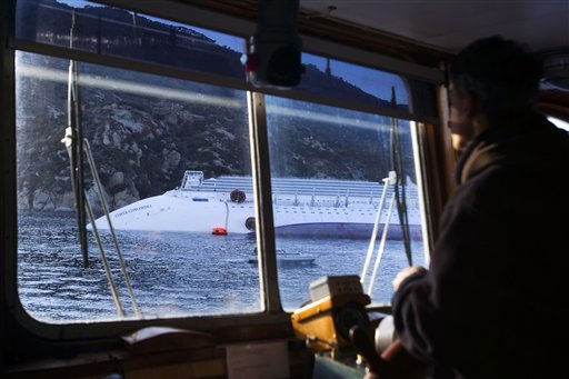 The cruise ship Costa Concordia is seen from an approaching ferry boat, laying on its side off the tiny Tuscan island of Giglio, Italy, Wednesday, Jan. 18, 2012. Italian searchers suspended operations on Wednesday after the enormous cruise ship grounded and partially submerged off the coast of Tuscany shifted slightly, creating concerns for the safety of divers and firefighters scouring the cruiseline for more than 20 passengers and crew still missing. &#40;AP Photo&#47;Angelo Carconi&#41; <span class=meta>(AP Photo&#47; Angelo Carconi)</span>