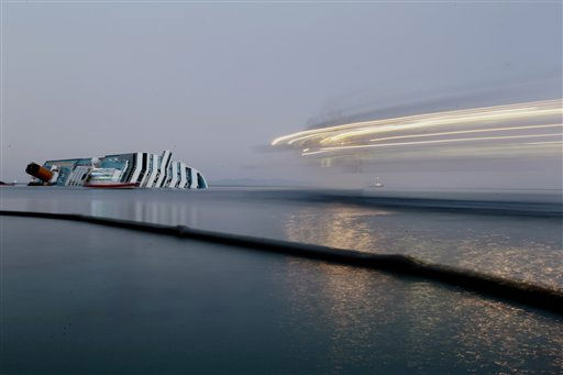 "<div class=""meta ""><span class=""caption-text "">In this photo made using a long exposure, a ferry boat, at right. passes past the cruise ship Costa Concordia leaning on its side after running aground the tiny Tuscan island of Giglio, Italy, Wednesday, Jan. 18, 2012. In foreground, a floating barrier is used to prevent an eventual oil spill from the ship. In response to a question at a press conference in London, Italian premier Mario Monti acknowledged Wednesday concern about a potential leak of the 500,000 gallons of fuel aboard the ship. He says authorities had made limiting and preventing leaks a priority, as well as caring for victims. (AP Photo/Gregorio Borgia) (AP Photo/ Gregorio Borgia)</span></div>"