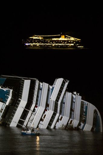 The cruise ship Costa Serena passes offshore as its sister ship Costa Concordia lays on its side off the tiny Tuscan island of Giglio, Italy, Wednesday, Jan. 18, 2012. The &#36;450 million Costa Concordia cruise ship was carrying more than 4,200 passengers and crew when it slammed into a reef Friday off the tiny Italian island of Giglio after the captain made an unauthorized maneuver. The death toll stands at 11, with 22 people still missing. &#40;AP Photo&#47;Angelo Carconi&#41; <span class=meta>(AP Photo&#47; Angelo Carconi)</span>