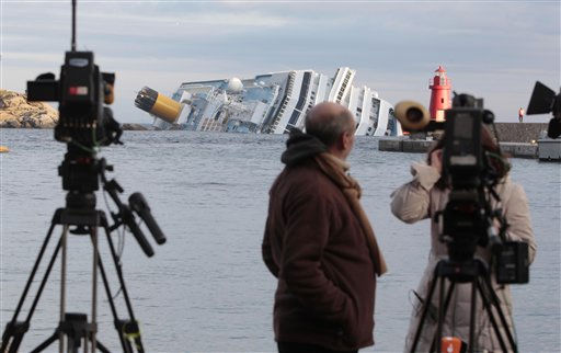 TV crews prepare to go on air as the cruise ship Costa Concordia is seen in background off the tiny Tuscan island of Giglio, Italy, Wednesday, Jan. 18, 2012.   <span class=meta>(AP Photo&#47; Gregorio Borgia)</span>