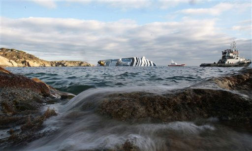 The cruise ship Costa Concordia lays on its side off the tiny Tuscan island of Giglio, Italy, Wednesday, Jan. 18, 2012. Search teams have suspended operations after an enormous cruise ship grounded and partially submerged off the coast of Tuscany shifted under turbulent seas.  <span class=meta>(AP Photo&#47; Gregorio Borgia)</span>