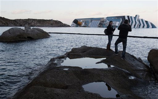 People take photographs of the grounded Costa Concordia cruise ship off the tiny Tuscan island of Giglio, Italy, Friday, Jan. 20, 2012. The cruise ship grounded off Tuscany shifted again on its rocky perch Friday, forcing the suspension of diving search operations for the 21 people still missing and raising concerns about the stability of the ship&#39;s resting place. &#40;AP Photo&#47;Gregorio Borgia&#41; <span class=meta>(AP Photo&#47; Gregorio Borgia)</span>