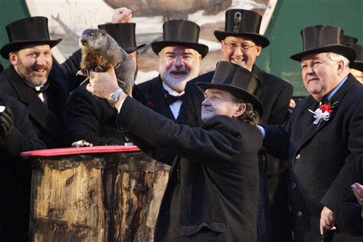 "<div class=""meta ""><span class=""caption-text "">Groundhog Club handler John Griffiths, center,  holds Punxsutawney Phil, the weather prognosticating groundhog, during the 126th celebration of Groundhog Day on Gobbler's Knob in Punxsutawney, Pa. Thursday, Feb. 2, 2012. Phil saw his shadow, forecasting six more weeks of winter weather.   (AP Photo/ Gene J. Puskar)</span></div>"