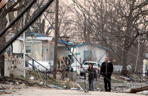 Residents walk amid downed power lines in their neighborhood in Branson, Mo, Wednesday, Feb.  29, 2012.  A powerful storm system  lashed the Midwest early Wednesday, roughing up the country music resort city of Branson and laying waste to a small town in Kansas. <span class=meta>(AP Photo&#47; Mark Schiefelbein)</span>