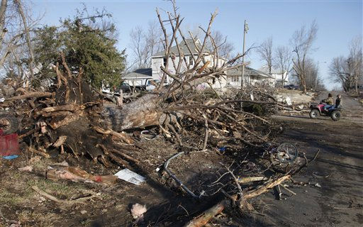 Residents ride past a tree that was downed by severe storms that destroyed several homes and businesses in Harveyville, Kan., Wednesday, Feb. 29, 2012.   <span class=meta>(AP Photo&#47; Orlin Wagner)</span>