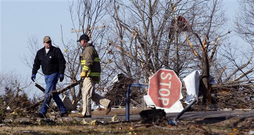 Volunteers walk past storm damage in Harveyville, Kan., Wednesday, Feb. 29, 2012. A powerful storm system  lashed the Midwest early Wednesday, roughing up the country music resort city of Branson and laying waste to the small town in Kansas.   <span class=meta>(AP Photo&#47; Orlin Wagner)</span>