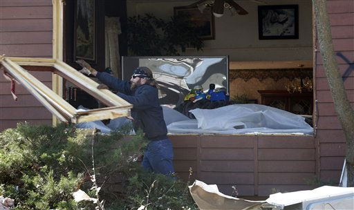 An unidentified man clears storm damage the morning after severe storms destroyed several homes and businesses in Harveyville, Kan., Wednesday, Feb. 29, 2012.  A powerful storm system  lashed the Midwest early Wednesday, roughing up the country music resort city of Branson and laying waste the  small town in Kansas.  <span class=meta>(AP Photo&#47; Orlin Wagner)</span>