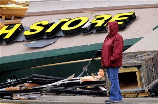 "<div class=""meta ""><span class=""caption-text "">Tammy Jenkins take time from cleaning up to survey the damage to a strip mall Friday, March 2, 2012, in Harrisburg, Ill.   A pre-dawn twister flattened entire blocks of homes Wednesday as violent storms ravaged the Midwest and South.  (AP Photo/Seth Perlman) (AP Photo/ Seth Perlman)</span></div>"