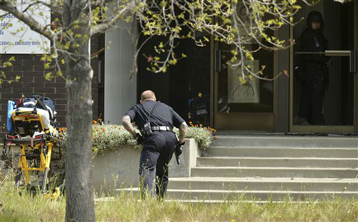 An Oakland police officer approaches the entrance to Oikos University in Oakland, Calif., Monday, April 2, 2012. A suspect was detained Monday in a shooting attack at a California Christian university that sources said has left at least five people dead. &#40;AP Photo&#47;Noah Berger&#41; <span class=meta>(AP Photo&#47; Noah Berger)</span>