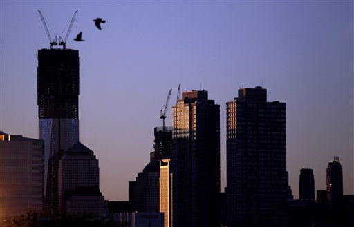 Viewed from Jersey City, N.J., two birds fly by as the sun rises over buildingsin New York, including One World Trade Center, tallest building at left, Monday, April 30, 2012. One World Trade Center, the giant monolith being built to replace the twin towers destroyed in the Sept. 11 attacks, will lay claim to the title of New York City&#39;s tallest skyscraper on Monday.  &#40;AP Photo&#47;Julio Cortez&#41; <span class=meta>(AP Photo&#47; Julio Cortez)</span>