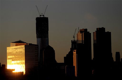 "<div class=""meta ""><span class=""caption-text "">The sun reflects on a building as it rises Monday April 30, 2012, including One World Trade Center, center left, in New York as seen from Jersey City, N.J. One World Trade Center, the giant monolith being built to replace the twin towers destroyed in the Sept. 11 attacks, will lay claim to the title of New York City's tallest skyscraper on Monday.   (AP Photo/Julio Cortez) (AP Photo/ Julio Cortez)</span></div>"