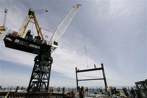 A crane on the top deck of One world Trade Center holds a steel beam between two columns to make the tower New York City&#39;s tallest skyscraper, Monday, April 30, 2012 in New York. One World Trade Center is being built to replace the twin towers destroyed in the Sept. 11 attacks. It reached just over 1,250 feet on Monday. That&#39;s just taller than the observation deck on the Empire State Building. &#40;AP Photo&#47;Mark Lennihan, Pool&#41; <span class=meta>(AP Photo&#47; Mark Lennihan)</span>