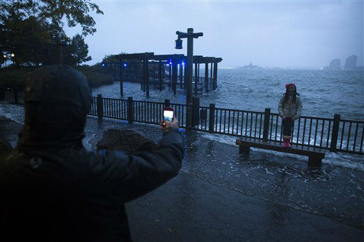 Maya Vaknin, 12, of Manhattan, poses for a picture with her father in front of the rising tides near Battery Park as the Hudson River spills over its banks, Monday, Oct. 29, 2012, in New York. Sandy continued on its path Monday, as the storm forced the shutdown of mass transit, schools and financial markets, sending coastal residents fleeing, and threatening a dangerous mix of high winds and soaking rain.? &#40;AP Photo&#47; John Minchillo&#41; <span class=meta>(AP Photo&#47; John Minchillo)</span>