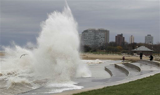 Onlookers take photos as strong waves created by superstorm Sandy crash against the Lake Michigan waterfront, Tuesday, Oct. 30, 2012, on the south side of Chicago. Strong winds from the outer edge of superstorm Sandy are ripping up near-record high waves on Lake Michigan.   <span class=meta>(AP Photo&#47; M. Spencer Green)</span>