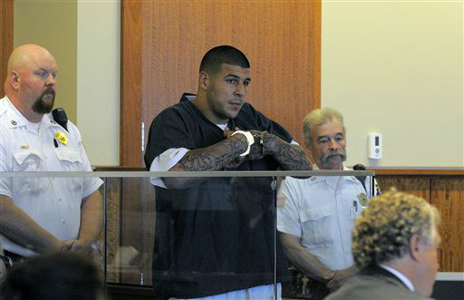 "<div class=""meta image-caption""><div class=""origin-logo origin-image ""><span></span></div><span class=""caption-text"">Former New England Patriots football tight end Aaron Hernandez stands during a bail hearing in Fall River Superior Court Thursday, June 27, 2013 in Fall River, Mass. Hernandez, charged with murdering Odin Lloyd, a 27-year-old semi-pro football player, was denied bail.   (AP Photo/ Ted Fitzgerald)</span></div>"