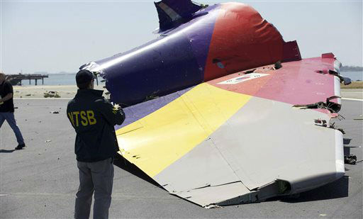 This image released by the National Transportation Safety Board, Sunday, July 7, 2013, shows an NTSB agent photographing a part of the Boeing 777 Asiana Airlines Flight 214 aircraft. The Asiana flight crashed upon landing Saturday, July 6, at San Francisco International Airport, and two of the 307 passengers aboard were killed.  <span class=meta>(AP Photo&#47; Uncredited)</span>