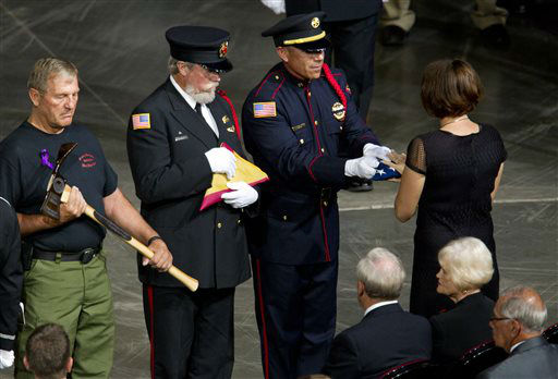 A flag is presented to Juliann Ashcraft, widow of fallen firefighter Andrew Ashcraft, during a memorial service for the 19 fallen firefighters at Tim&#39;s Toyota Center in Prescott Valley, Ariz. on Tuesday, July 9, 2013.   Prescott&#39;s Granite Mountain Hotshots were overrun by smoke and fire while battling a blaze on a ridge in Yarnell, about 80 miles northwest of Phoenix on June 30, 2013.    <span class=meta>(AP Photo&#47; MICHAEL CHOW)</span>