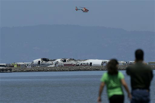 A helicopter flies above the wreckage of Asiana Flight 214 after it crashed at San Francisco International Airport in San Francisco, Saturday, July 6, 2013.   <span class=meta>(AP Photo&#47; Jeff Chiu)</span>