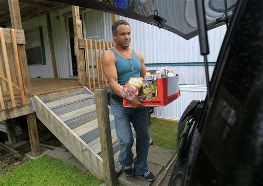 Estanislao Fabian loads food into their car as they evacuate their home in advance of Tropical Storm Isaac, which is expected to make landfall in the region as a hurricane this evening in Plaquemines Parish, La.,  Tuesday, Aug. 28, 2012.  Forecasters at the National Hurricane Center warned that Isaac, especially if it strikes at high tide, could cause storm surges of up to 12 feet &#40;3.6 meters&#41; along the coasts of southeast Louisiana and Mississippi and up to 6 feet &#40;1.8 meters&#41; as far away as the Florida Panhandle.  <span class=meta>(AP Photo&#47; Gerald Herbert)</span>