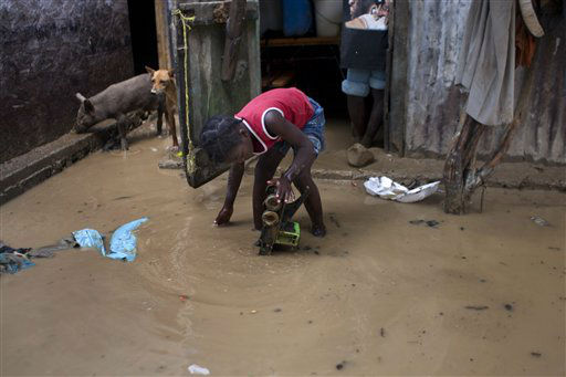 A girl recovers a toy from muddy waters at her flooded house after the passing of Tropical Storm Isaac in Port-au-Prince, Haiti, Sunday Aug. 26, 2012. The death toll in Haiti from Tropical Storm Isaac has climbed to seven after an initial report of four deaths, the Haitian government said Sunday.  <span class=meta>(AP Photo&#47; Dieu Nalio Chery)</span>