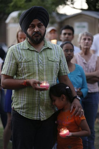 Mourners take part in a candle light vigil for the victims of the Sikh Temple of Wisconsin shooting, in Milwaukee, Sunday, Aug 5, 2012. An unidentified gunman killed six people at a Sikh temple in suburban Milwaukee in a rampage that left terrified congregants hiding in closets and others texting friends outside for help. The suspect was killed outside the temple in a shootout with police officers.   <span class=meta>(AP Photo&#47; JEFFREY PHELPS)</span>