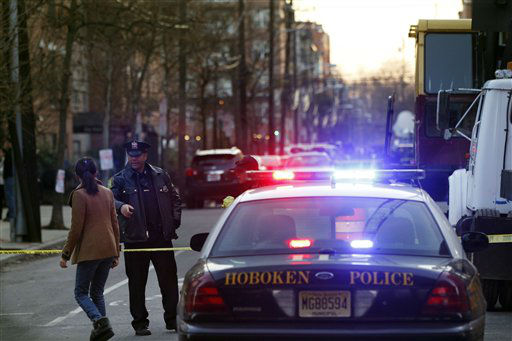 A Hoboken police officer stands at a blocked street near a residence at the intersection of 13th and Grand streets in Hoboken, N.J. on Friday, Dec. 14, 2012 after a connection was reported with the shootings at the Sandy Hook Elementary School in Newtown, Conn.   <span class=meta>(AP Photo&#47; Mel Evans)</span>