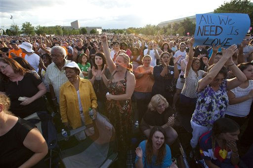 Stacy Moriarty, center left, raises her hand as she she joins thousand in a unified cheer as Gov. John Hickenlooper speaks during a vigil, Sunday, July 22, 2012, at the Aurora Municipal Center in Aurora, Colo., for the victims of Friday&#39;s mass shooting a movie theater. Twelve people were killed and dozens were injured in a shooting attack early Friday at the packed theater during a showing of the Batman movie, &#34;The Dark Knight Rises.&#34; Police have identified the suspected shooter as James Holmes, 24. &#40;AP Photo&#47;Barry Gutierrez&#41; <span class=meta>(AP Photo&#47; Barry Gutierrez)</span>