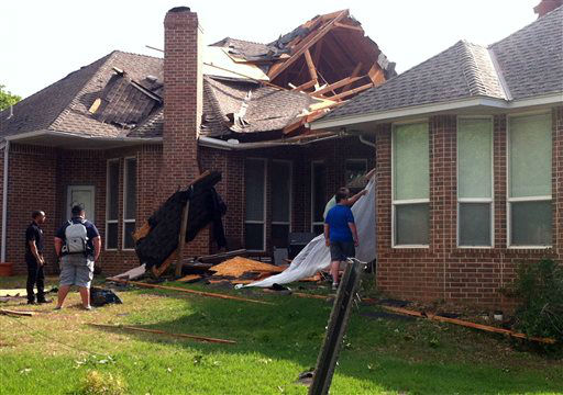 Residents of Edmond, Okla., survey storm damage from a tornado that hit their neighborhood Sunday, May 19, 2013. Forecasters had warned that the middle of the country would see severe weather throughout the weekend.   <span class=meta>(AP Photo&#47; Sean Murphy)</span>