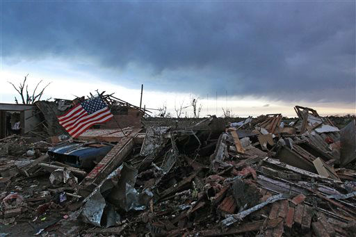 "<div class=""meta image-caption""><div class=""origin-logo origin-image ""><span></span></div><span class=""caption-text"">An American flag blows in the wind at sunrise atop the rubble of a destroyed home a day after a tornado moved through Moore, Okla., Tuesday, May 21, 2013. The monstrous tornado roared through the Oklahoma City suburb Monday, flattening entire neighborhoods and destroying an elementary school with a direct blow as children and teachers huddled against winds up to 200 mph. (AP Photo/Brennan Linsley) (AP Photo/ Brennan Linsley)</span></div>"