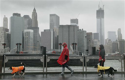 Peter Cusack, center, and Mel Bermudez walk their dogs Teague, left, and Molly along the Brooklyn waterfront beneath the New York skyline as Hurricane Sandy advances on the city, Monday, Oct. 29, 2012. Hurricane Sandy continued on its path Monday, forcing the shutdown of mass transit, schools and financial markets, sending coastal residents fleeing, and threatening a dangerous mix of high winds and soaking rain.? &#40;AP Photo&#47;Mark Lennihan&#41; <span class=meta>(AP Photo&#47; Mark Lennihan)</span>
