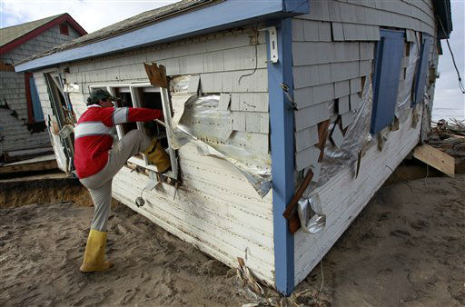 Christopher Hannafin, of South Kingstown, R.I., enters a friend&#39;s cottage through a window to salvage belongings from the structure destroyed by Superstorm Sandy, on Roy Carpenter&#39;s Beach, in the village of Matunuck, in South Kingstown, Tuesday, Oct. 30, 2012. Sandy, the storm that made landfall Monday, caused multiple fatalities, halted mass transit and cut power to more than 6 million homes and businesses.   <span class=meta>(AP Photo&#47; Steven Senne)</span>