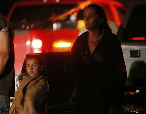 Seven-year-old Katrina Ash, left, watches with her mother, Amber Ash, right, as heavy equipment is brought into their tornado damaged neighborhood near Dale, Okla., Sunday, May 19, 2013. Residents are not being allowed into the neighborhood as search and rescue operations continue. &#40;AP Photo Sue Ogrocki&#41; <span class=meta>(AP Photo&#47; Sue Ogrocki)</span>