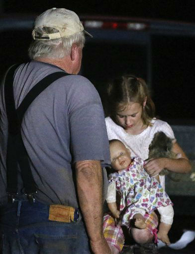 Seven-year-old Katrina Ash, right, holds a doll as she waits with her grandfather, Michael Bowen, left, after a tornado ripped through their neighborhood near Dale, Okla., Sunday, May 19, 2013. Residents are not being allowed back into the neighborhood as search and rescue efforts take place. &#40;AP Photo Sue Ogrocki&#41; <span class=meta>(AP Photo&#47; Sue Ogrocki)</span>