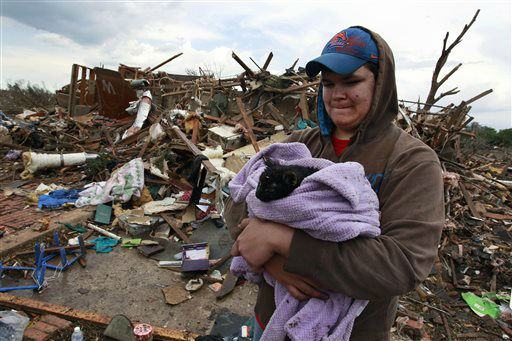Austin Brock holds cat Tutti, shortly after the animal was retrieved from the rubble of Brock&#39;s home, which was demolished a day earlier when a tornado moved through Moore, Okla., Tuesday, May 21, 2013. A huge tornado roared through the Oklahoma City suburb Monday, flattening an entire neighborhoods and destroying an elementary school with a direct blow as children and teachers huddled against winds.  <span class=meta>(AP Photo&#47; Brennan Linsley)</span>